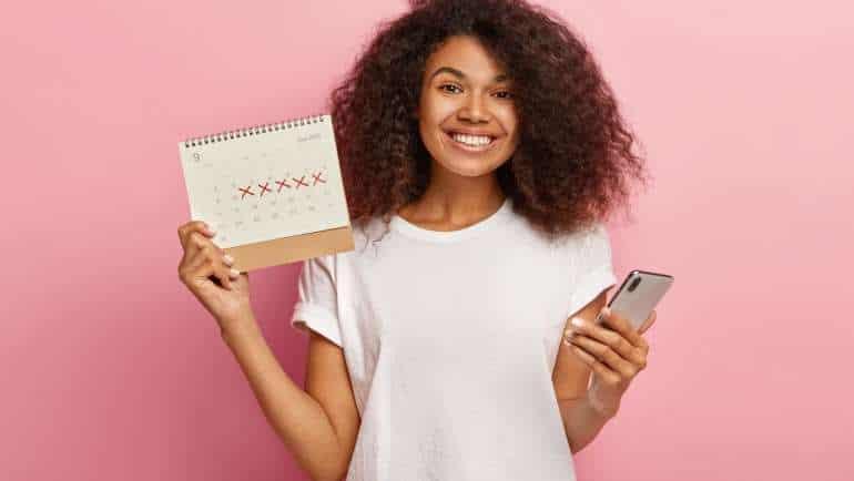 EaD - jovem negra sorri e segura calendário em uma mão e celular em outra