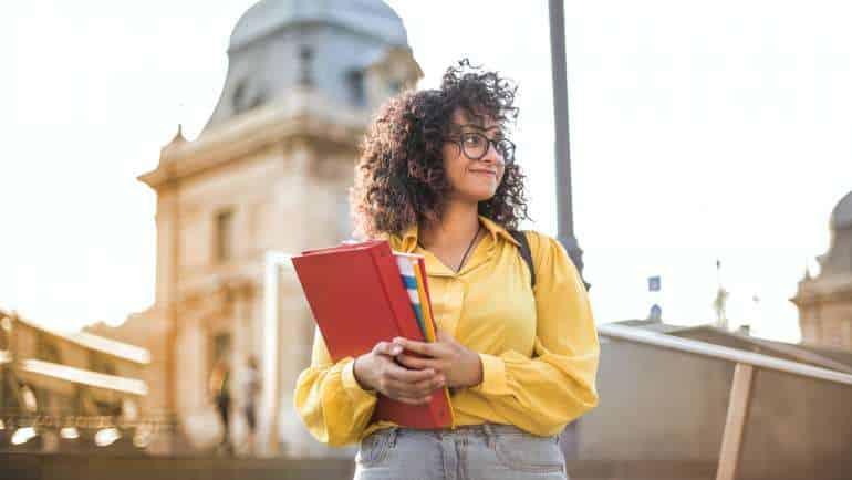 EAD - jovem de cabelo cacheado, blusa amarela e calça jeans segura cadernos em frente universidade, com fundo desfocado